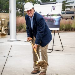 Randy Wise posing with shovel after breaking ground
