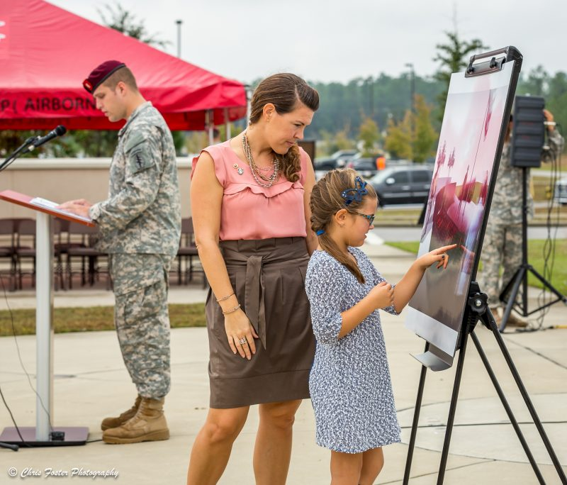 Little girl and her mother looking at the artist rendering