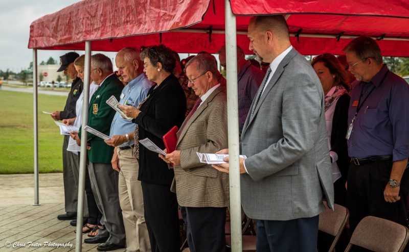 Guests standing up at the ceremony and reading from provided material