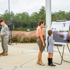 little girl and mom gazing at artistic rendering of memorial wall