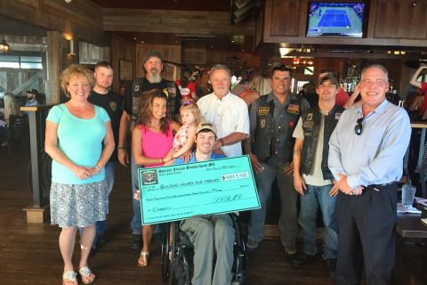The Military Motorcycle Club members presenting a large check to a man in a wheelchair