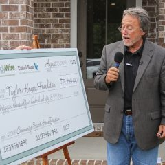 Randy Wise speaks to the audience about the large check