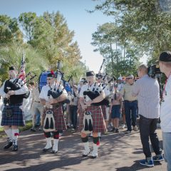 Pipers marching down the street playing bagpipes